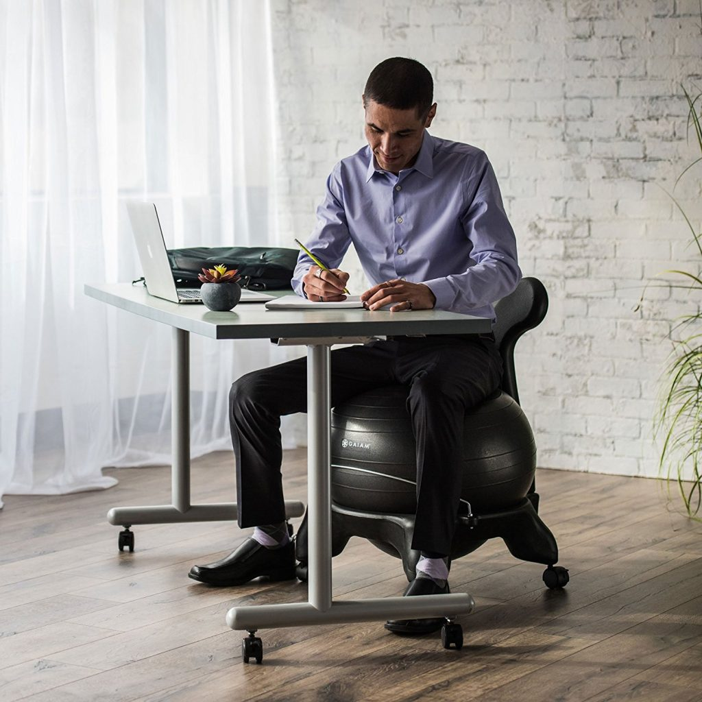 man sitting on the gaiam yoga ball while doing work