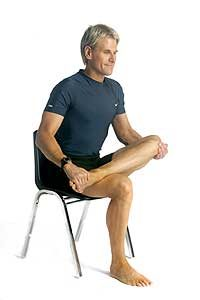 man doing desk exercises for lower back pain chair seated hip stretch