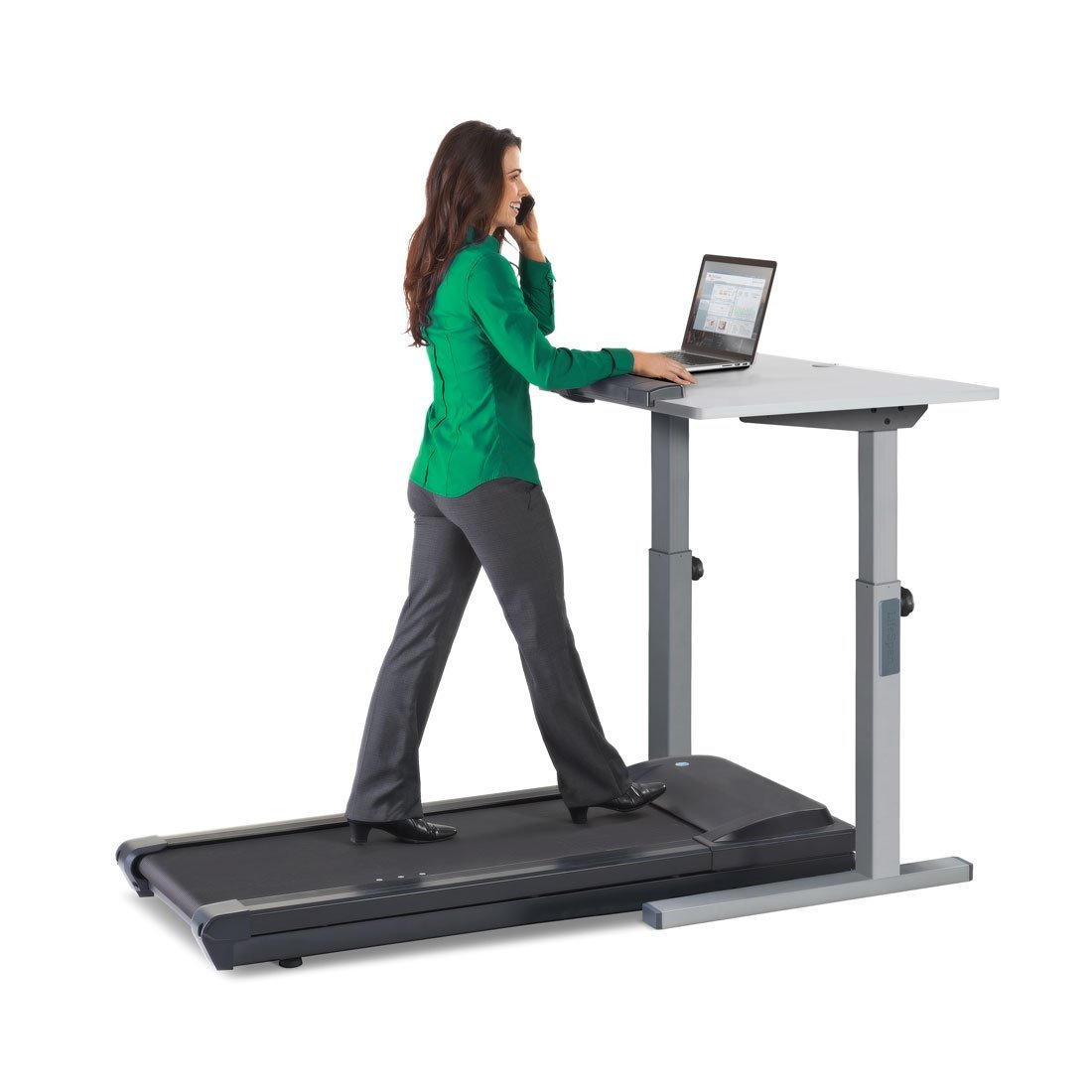 woman on the phone while walking on treadmill working on laptop desk
