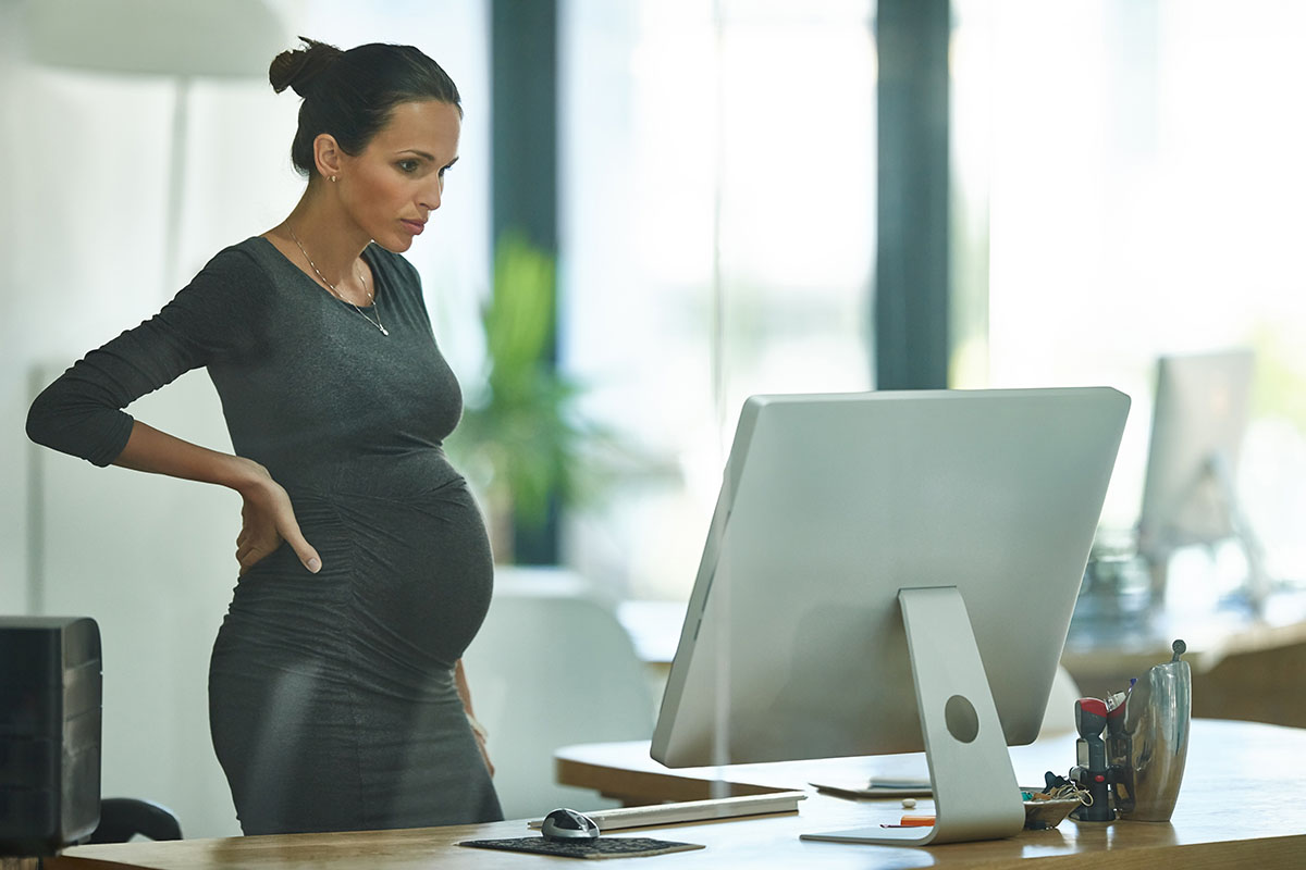 pregnant business woman standing up working in an office