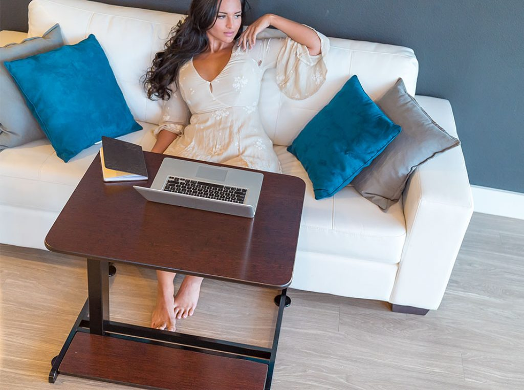 woman with an xdesk hybrid compact in living room sitting on a couch