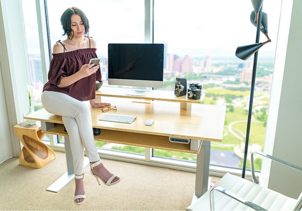 woman sitting on a xdesk terra stand up desk next to floor to ceiling windows