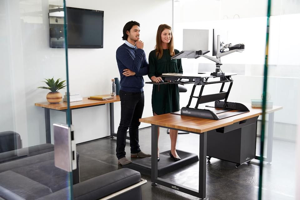 man and woman looking at a monitor screen using the varidesk stand up desk converter