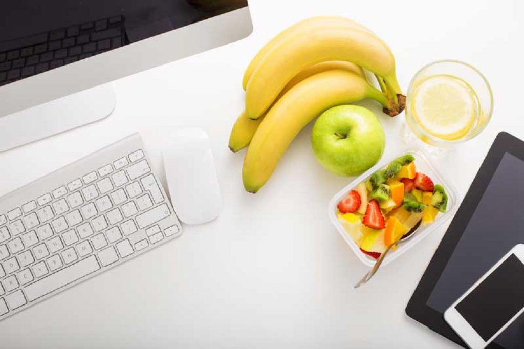 banana and apple snacks on a desk