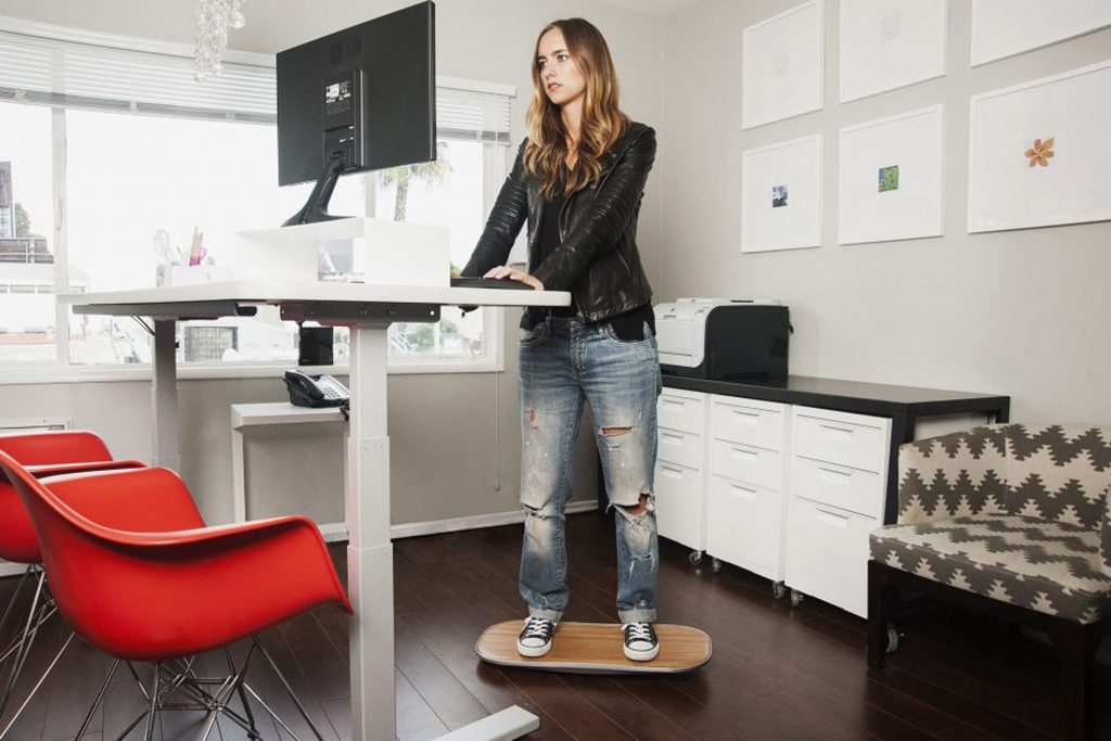 woman on a balancing device using a standing desk