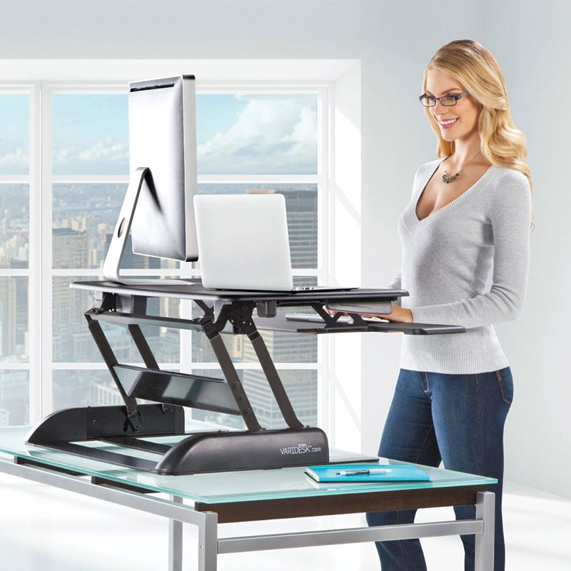 varidesk pro plus 36 woman using standing desk converter and working