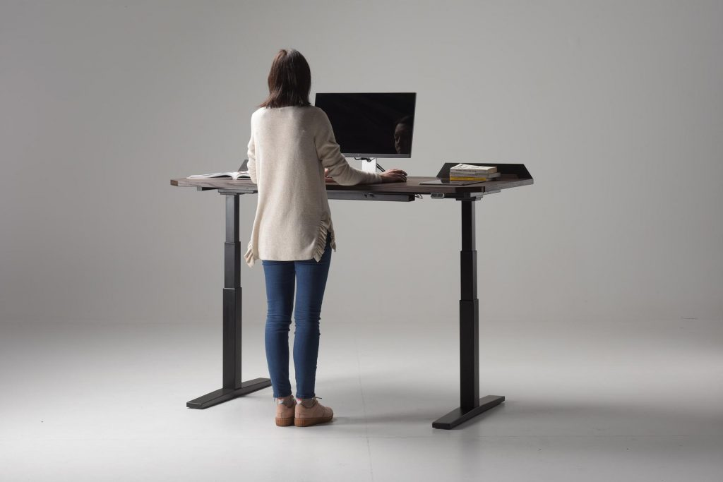 Woman using the UFO Lift Standing Desk