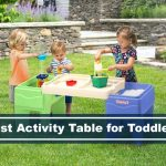 toddlers playing outside with an activity table