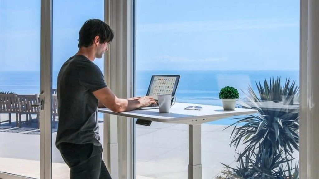 man using the autnomous ai standing desk with a view